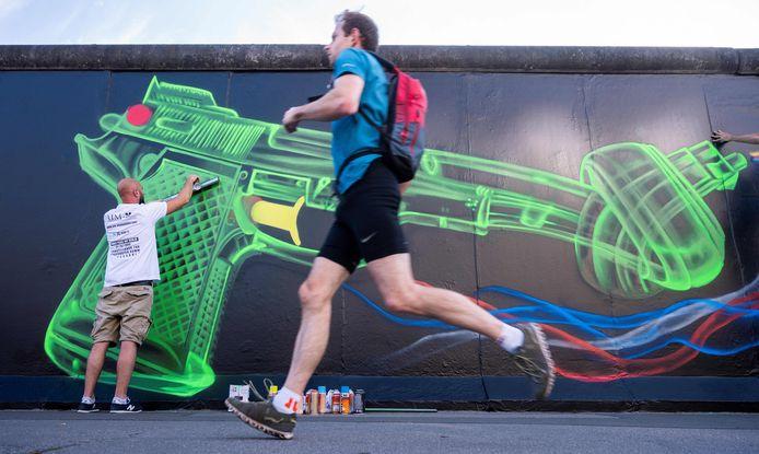 Een man rent voor een artiest langs, die op de Berlijnse muur een geupdate versie maakt van het beroemde kunstwerk 'Non-Violence', een pistool met een knoop erin.