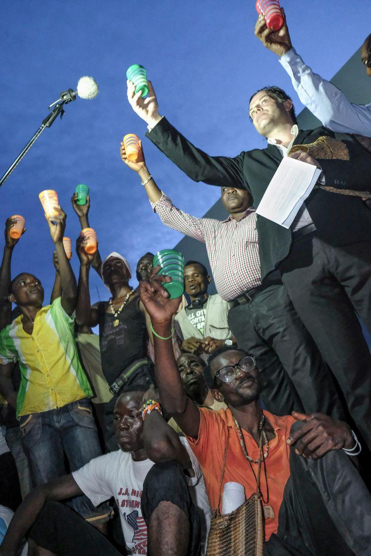 Renzo Martens (in zwart pak), de burgemeester (in overhemd) en kunstenaars proosten op de White Cube. Beeld Léonard Pongo