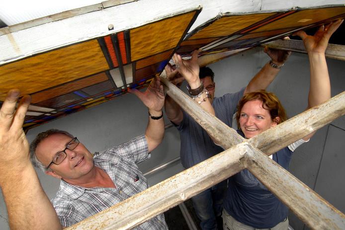 Karel Bartelen (links) bekijkt glas-in-lood ramen in een van de bijna 180 Hurks-panden in Roosendaal. Zaterdagavond werd hij Koninklijk onderscheiden.