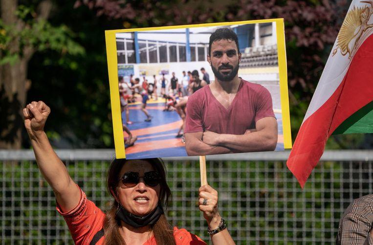 Een demonstrant houdt een foto van Navid Afkari omhoog bij de Iraanse ambassade in Berlijn. Beeld EPA