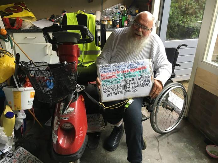 Arnol Kox in zijn rolstoel bij de scootmobiel die hij van de gemeente Eindhoven moet inleveren.