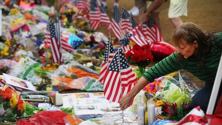 Een vrouw plaatst een Amerikaanse vlag op de gedenkplek voor de slachtoffers van aanslag op homonachtclub Pulse in Orlando. Beeld afp