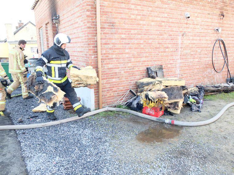 De brandweer haalt puin uit het huis.