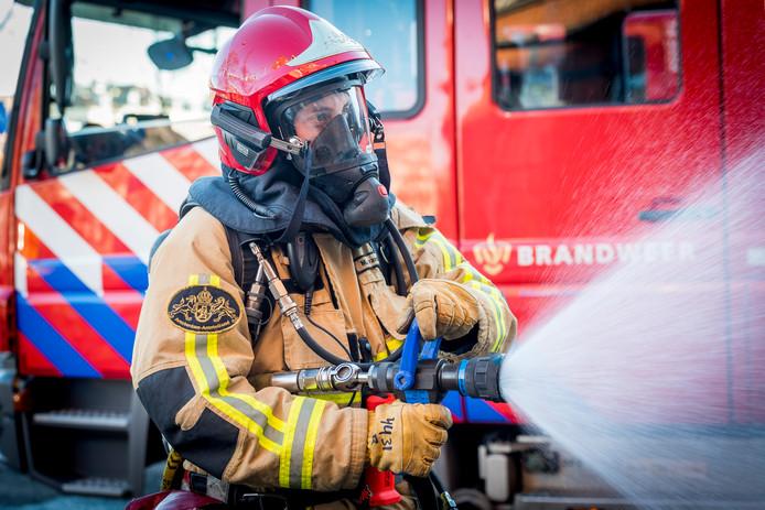 Brandweerman bezig met bluswerkzaamheden.
