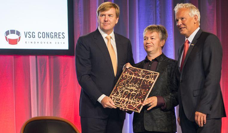 Koning Willem-Alexander neemt de heruitgave van het Sportalbum 1898 in ontvangst uit handen van Jurryt van de Vooren (midden) en Jan Rijpstra. Beeld anp
