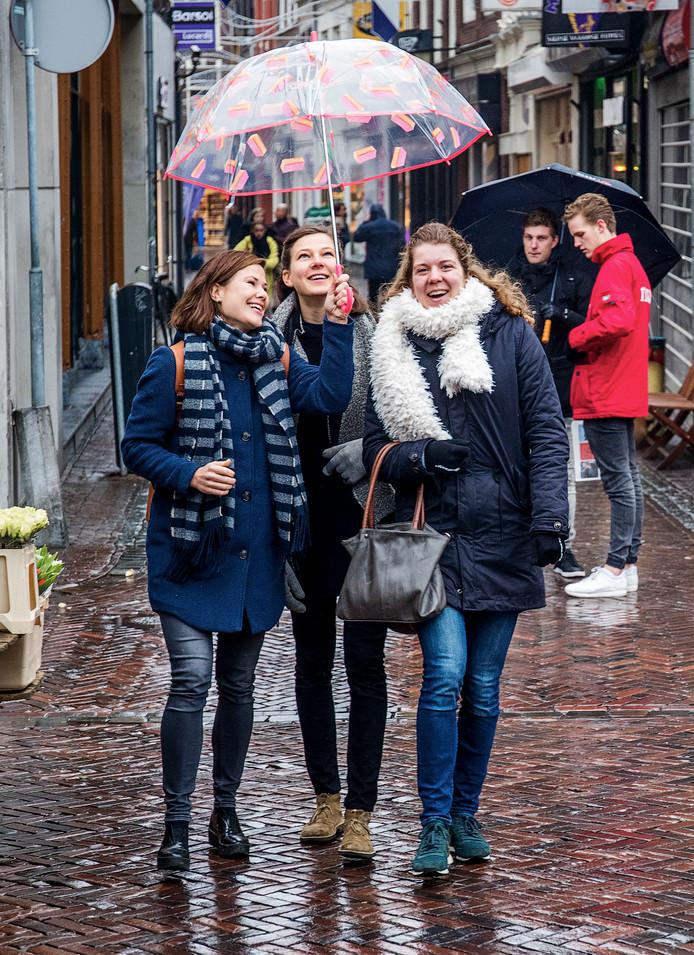 Rachel van de Pols spontane paraplulift leidt doorgaans tot lachende gezichten, zoals op de foto bij Karlijn Scheepens (rechts) en Laura Grootes.