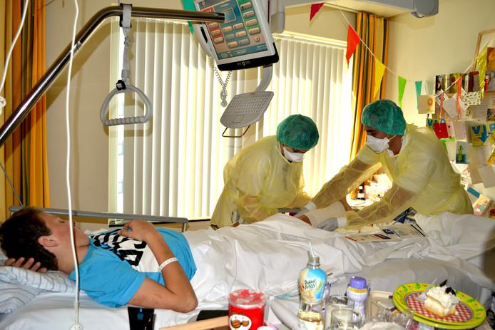 Een patiënt die de MRSA-bacterie bij zich draagt wordt behandeld door personeel in beschermende kleding.