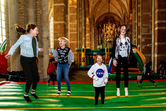 Jolien, Rosanne, Melle en Robine uit Luttenberg leven zich uit op de springkussens in de Grote Kerk.