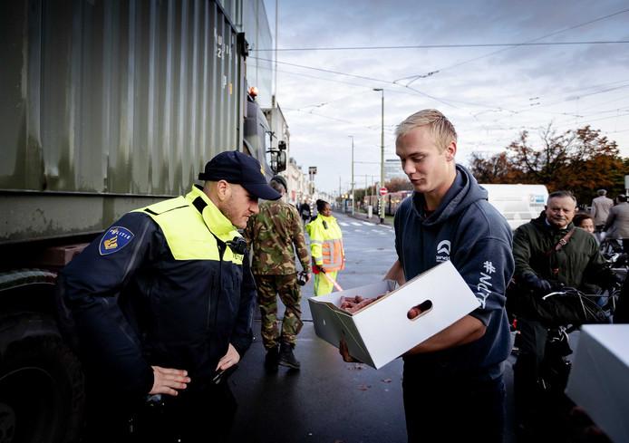 Boeren delen onderweg naar het boer-burgerontbijt eten uit aan een politieman. Farmer Defence Force organiseerde dit ontbijt om Nederlandse burgers te bedanken voor hun steun tijdens de protesten.