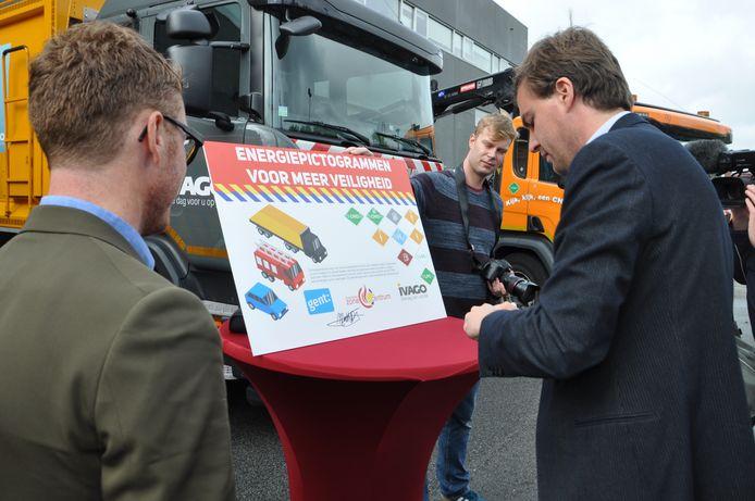 Burgemeester Mathias De Clercq en Bram Van Braeckevelt van IVAGO signeren.
