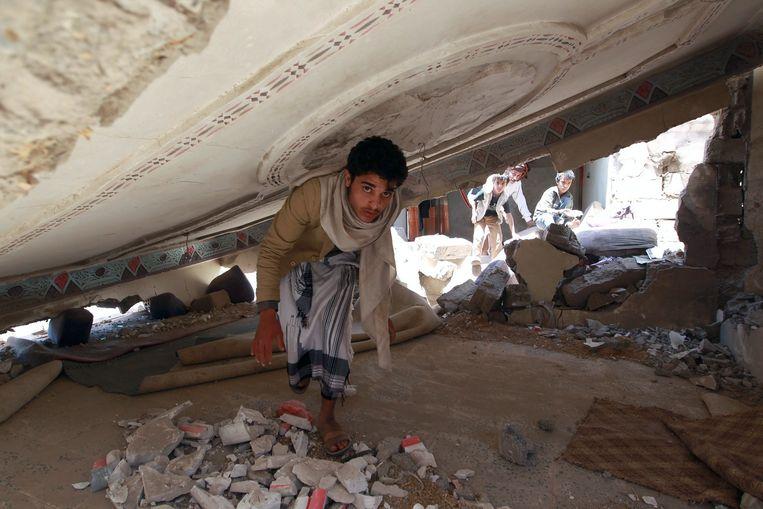 Een man kijkt rond in zijn huis dat is ingestort na een bombardement. Beeld afp