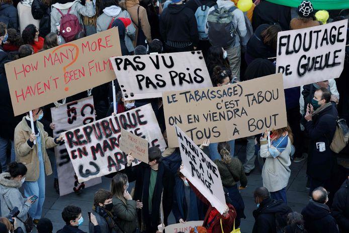 Demonstranten op de Place de la Republique in Parijs met borden met onder andere 'Niet gezien, niet gearresteerd', 'Hoeveel anderen zijn niet gefilmd?' en 'Blurren van de mond' .