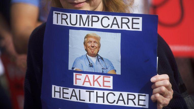 Een demonstrant houdt een bordje omhoog met 'Trumpcare is nepzorg' op een bijeenkomst eerder dit jaar. Beeld null