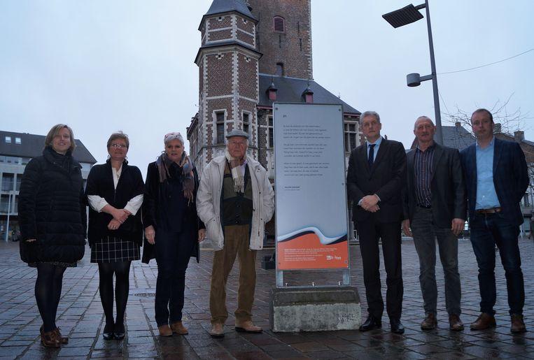 Walter Haesaert samen met vertegenwoordigers van het stadsbestuur aan zijn gedicht dat op de markt staat.