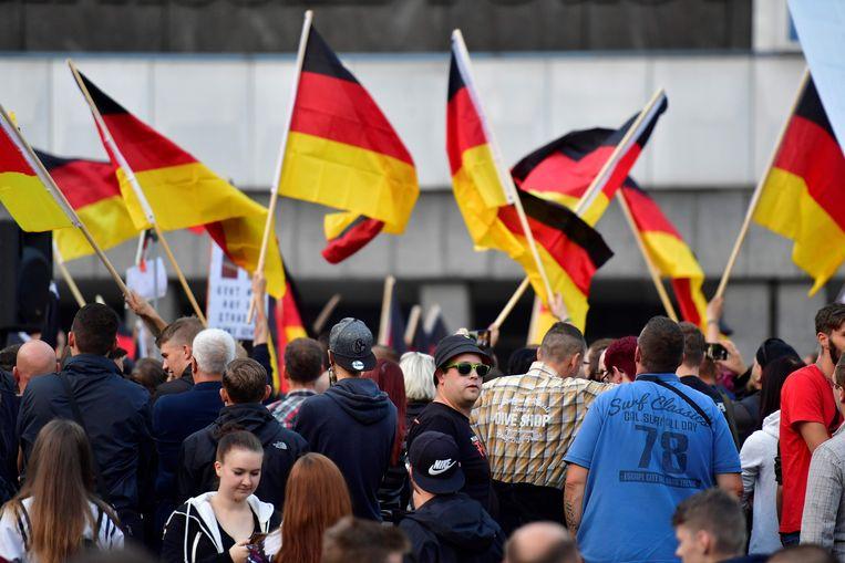 Mensen zwaaien met Duitse vlaggen tijdens de 'Pro Chemnitz' demonstraties.  Beeld AFP