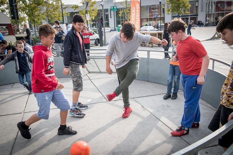 Kinderen amuseren zich met een spelletje voetbal tijdens de dag van het Jeugdwerk.