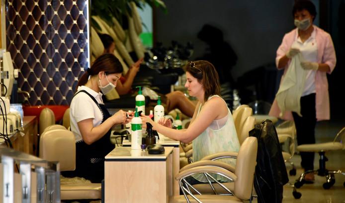 Een manicure aan het werk. (Archieffoto, de personen op de foto komen niet voor in het verhaal.)