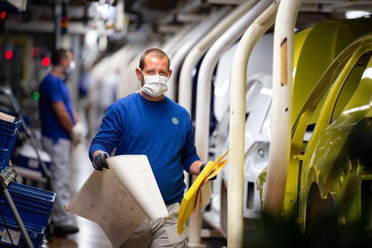 Medewerkers van de autofabriek in Wolfsburg zijn weer aan de slag, met handschoenen en maskers. De fabriek werd eind maart gesloten.  Beeld Getty Images