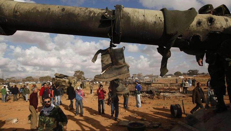 Laarzen van een soldaat van het leger van Kadafi hangen aan een tank die kapot is geschoten bij luchtaanvallen van het Westen. Beeld reuters