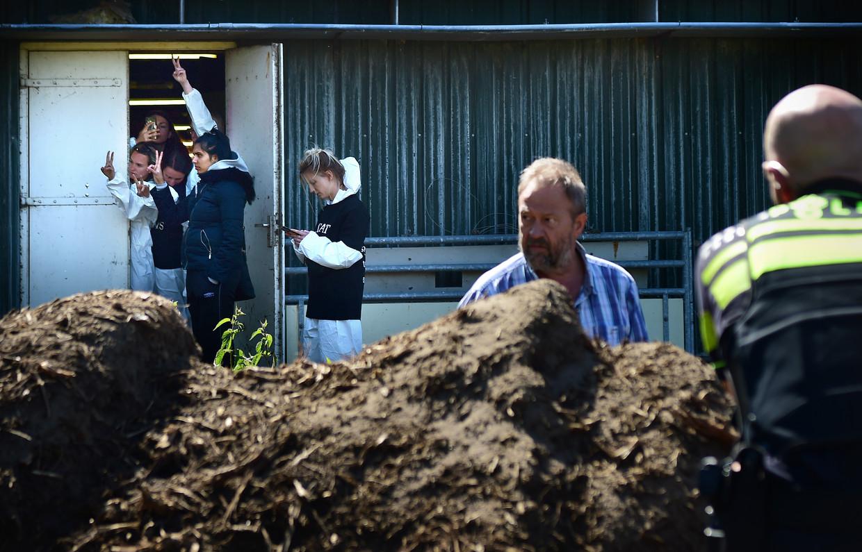Een boer overlegt maandag met een agent bij de bezette varkensstallen in Boxtel. Daarachter maken de actievoerders V-tekens. Beeld Marcel van den Bergh