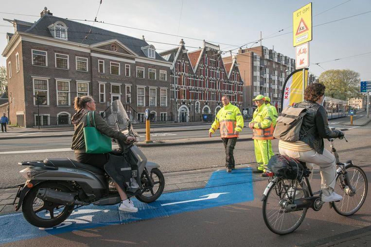 Bij het Waterlooplein in Amsterdam staan handhavers om de weg te wijzen. Er zijn speciale blauwe banen aangebracht Beeld Dingena Mol