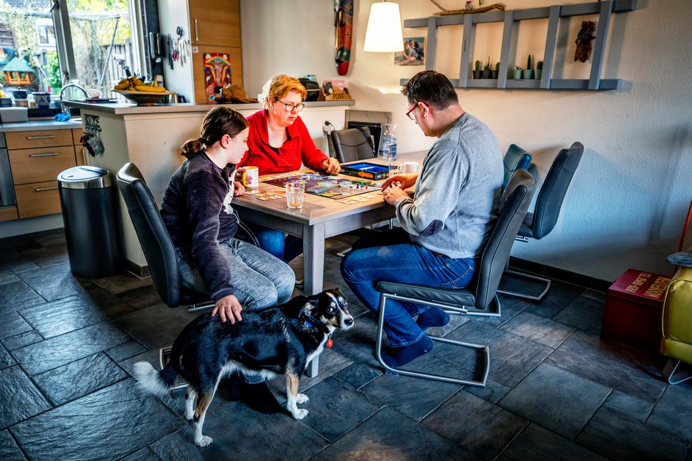 De familie Koning uit Hengelo speelt na het eten een potje Pandemic. Beeld Raymond Rutting / de Volkskrant