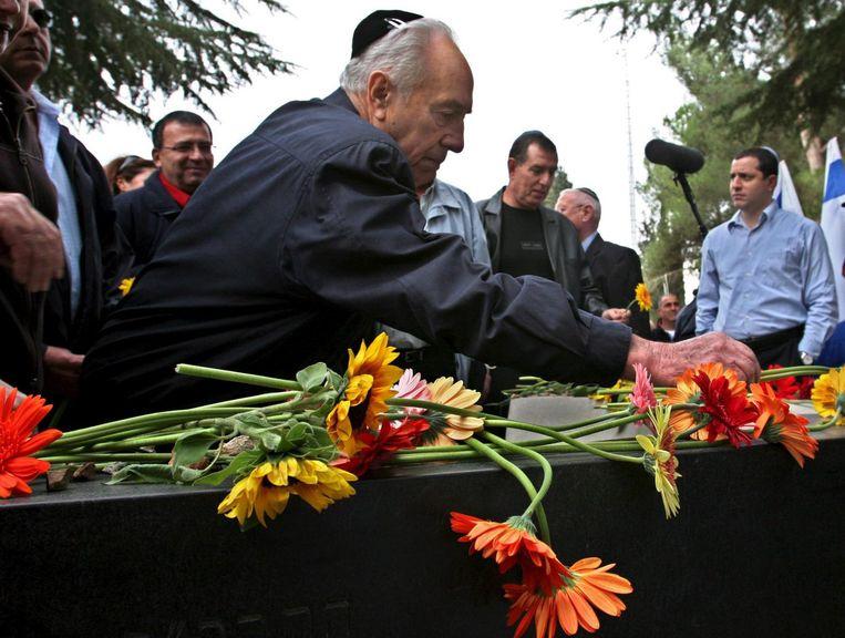 Peres legt in 2005 bloemen op het graf van Yitzhak Rabin, tien jaar eerder was vermoord door een extreem-rechtse jood in Tel Aviv. Beeld Photo News