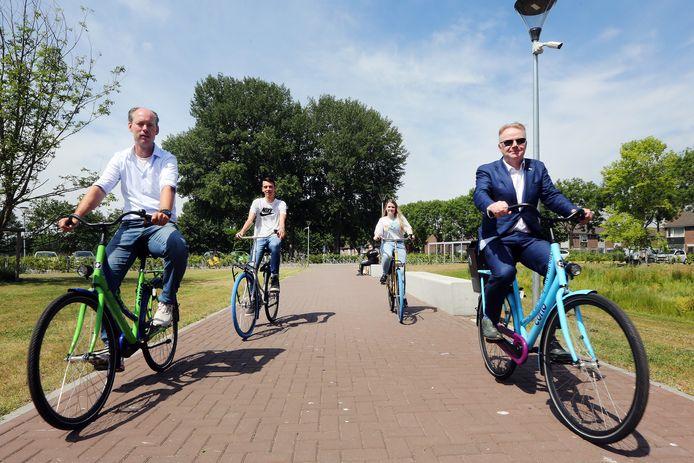 Wethouder Daan Quaars (l) en Rob Neutelings - voorzitter Raad van Bestuur Curio  doen een testrondje op de door Jordy Gideonse (achtergrond links) en Mirthe van Dijk gewrapte fietsen voor Curio.