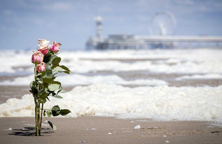 Bloemen tussen het schuim op het strand van Scheveningen. De badplaats is in rouw. Slecht weer heeft vijf surfers het leven gekost.  Beeld ANP