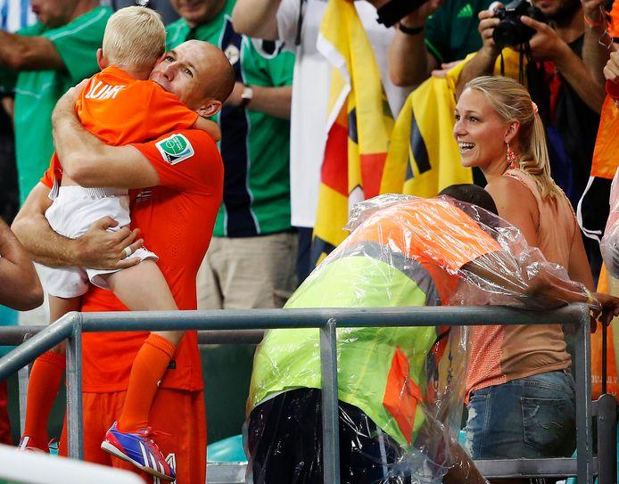 Bernadien Robben kijkt toe hun Arjen Robben hun zoontje Luka een knuffel geeft.