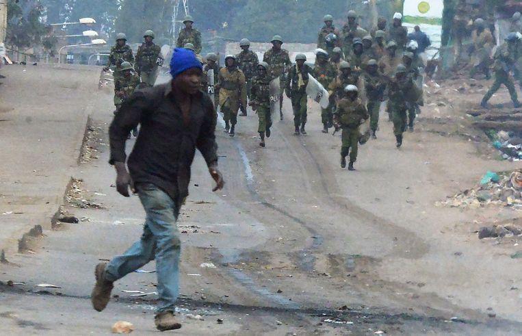 Een man rent weg van leden van de Keniaanse veiligheidsdienst tijdens een demonstratie in Kawangware, een sloppenwijk aan de westzijde van de hoofdstad Nairobi. Beeld AFP
