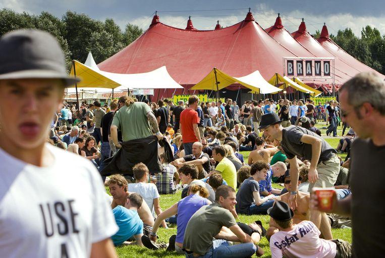 Bezoekers genieten vrijdag van de zon voor de Bravo tent op het festival met muziek- en theateracts. Foto ANP/Koen van Weel Beeld
