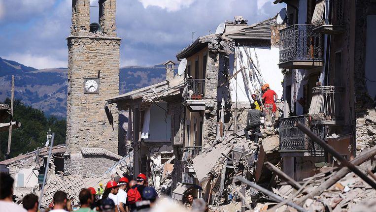 Brandweermannen en reddingswerkers in Amatrice, een van de getroffen plaatsen in Italië waar zeker 53 mensen omkwamen. Beeld afp