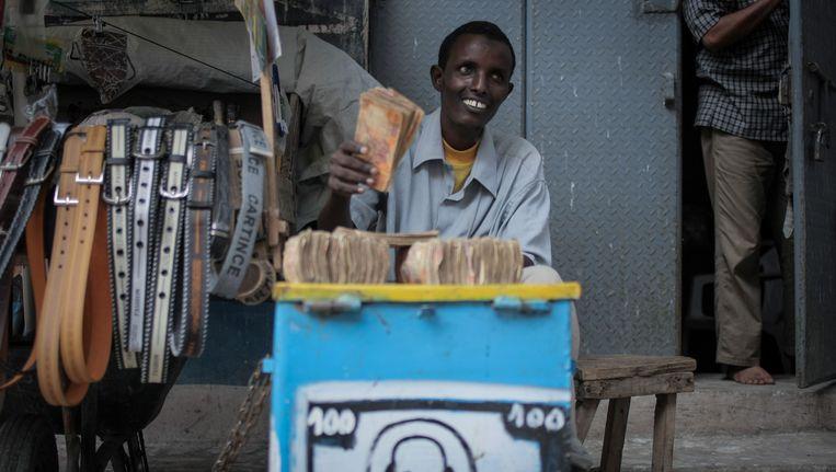 Een geldwisselaar in de Somalische hoofdstad Mogadishu betaalt familieleden de overmakingen van arbeidsmigranten in het Westen. Beeld afp