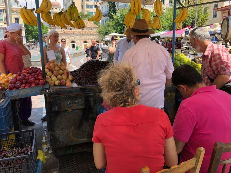 Belastinginspecteurs Vasia (rood shirt) en collega Thanasis  controleren bij een fruitkraam in Athene.  Beeld Thijs Kettenis