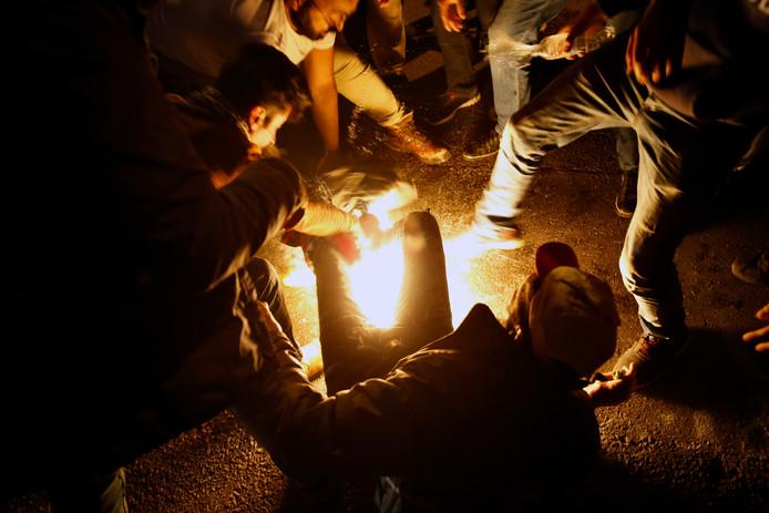Des manifestants ont éteint les flammes au niveau des jambes de l'homme à l'aide de vestes et de couvertures.