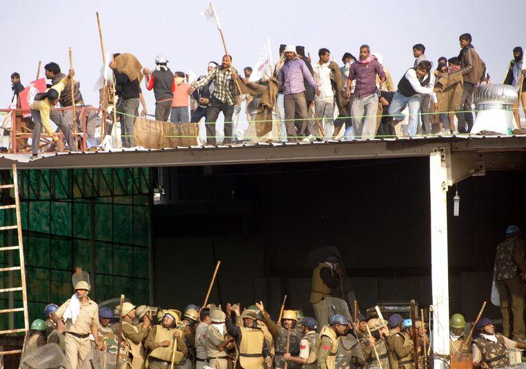 De aanhangers van de goeroe staan op het dak van zijn ashram, terwijl politieagenten het gebouw proberen binnen te dringen.