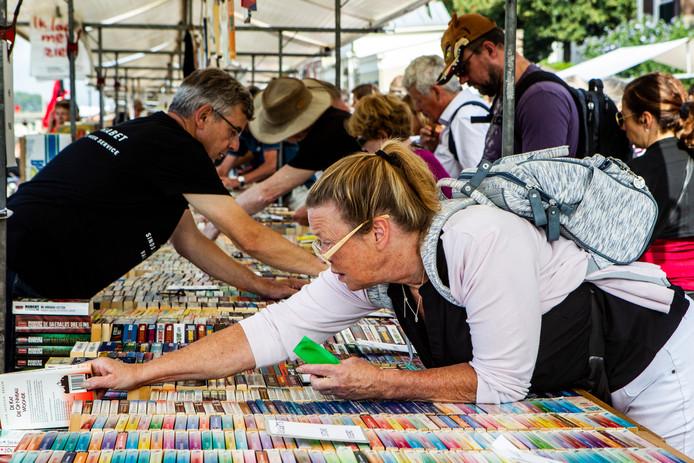 Een bezoekster van de Deventer Boekenmarkt legt een boek terug op een kraampje.