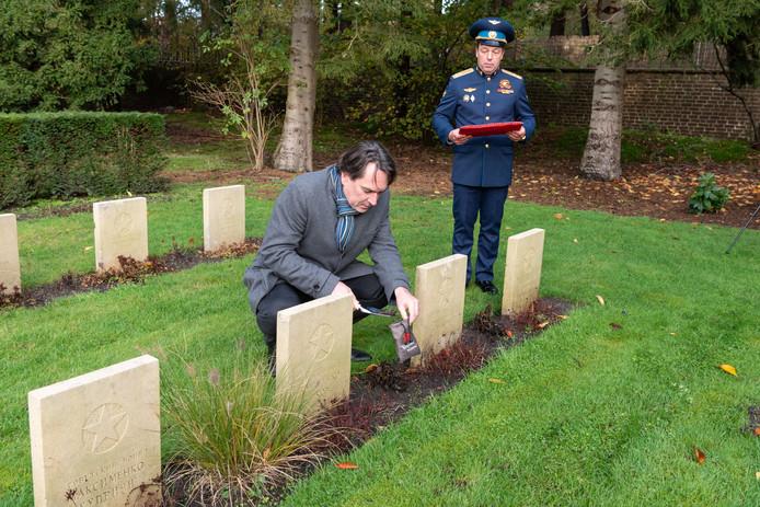 Remco Reiding deponeert aarde in een zakje dat hij aanbiedt aan ambassadeur en militair attaché Michail Klimoek.