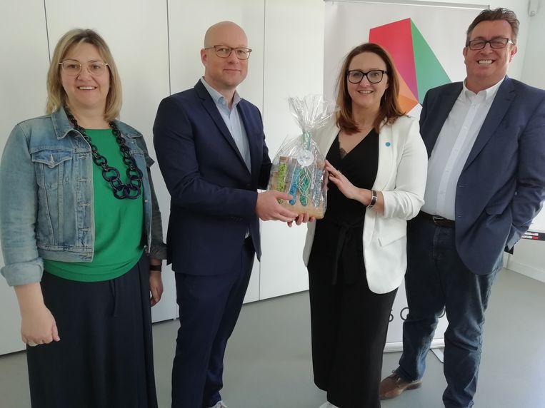 Ann Scheys en Gert Van Passel van Adite geven een welkomsgeschenk aan burgemeester Rutten en schepen van Onderwijs Geert Schellens.
