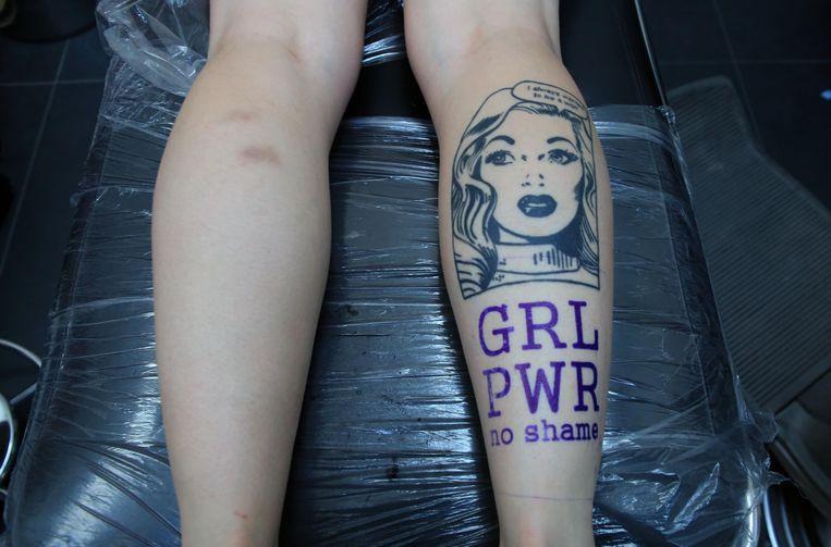 De gratis 'GRL PWR no shame'-tattoo wordt gecombineerd met het gezicht van een jonge vrouw.