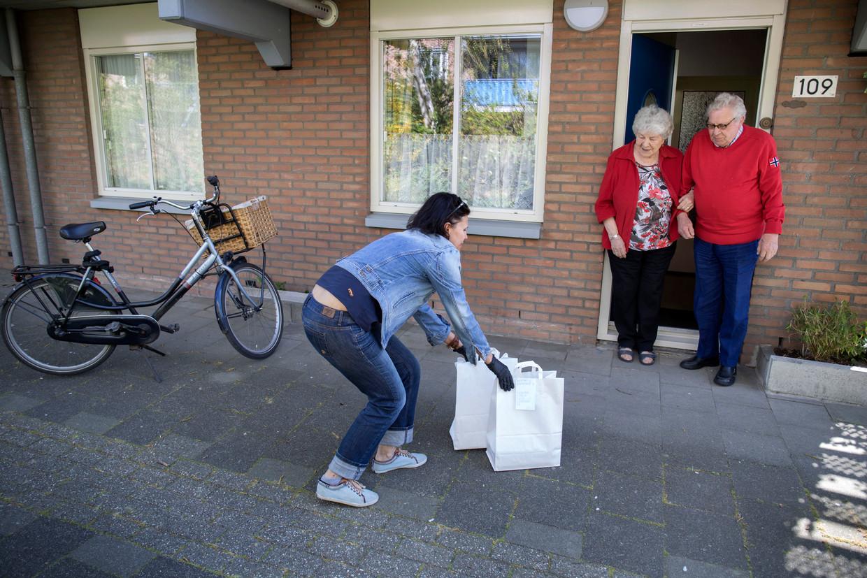 Bibliotheekmedewerkster Elena Lekveshvili brengt twee tasjes met boeken naar het echtpaar Van Gend.