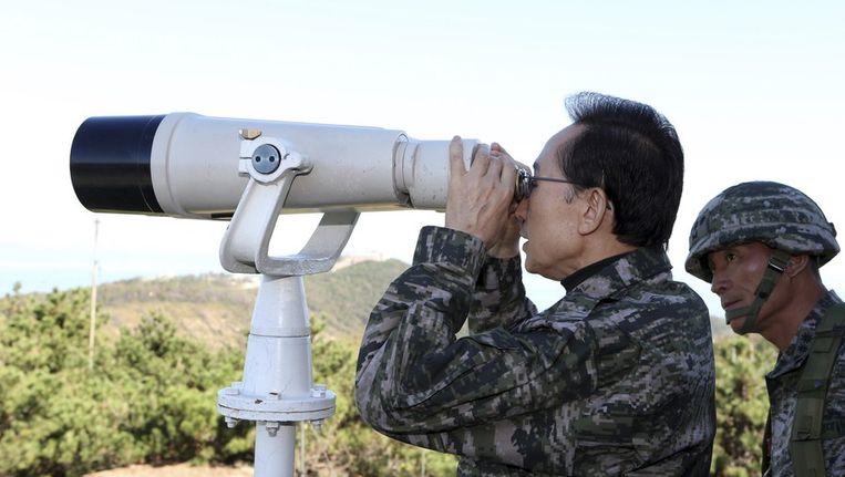 De Zuid-Koreaanse president Lee Myung-Bak kijkt naar Noord-Korea met een verrekijker. Beeld reuters