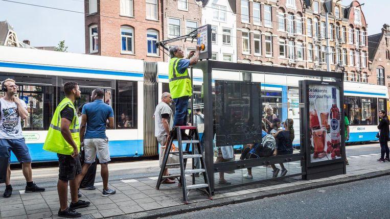 GVB-medewerker Fikri Cekici vervangt de dienstregelingen bij bus- en tramhaltes. Beeld Tammy van Nerum