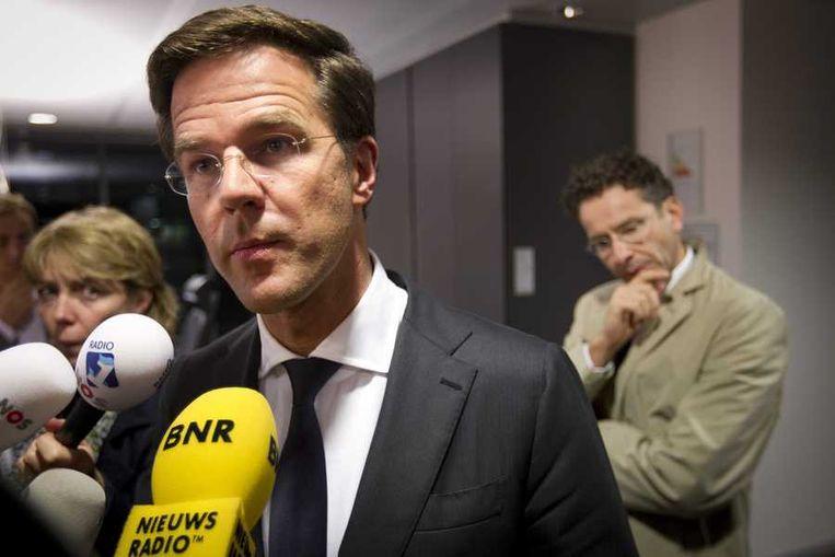 Premier Rutte staat na het nachtelijke overleg de pers te woord. Op de achtergrond minister van Financiën Dijsselbloem. Beeld anp