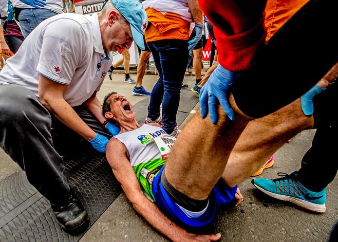 Vrijwilligers van het Rode Kruis helpen een hardloper na de finish van de Rotterdam Marathon 2018.