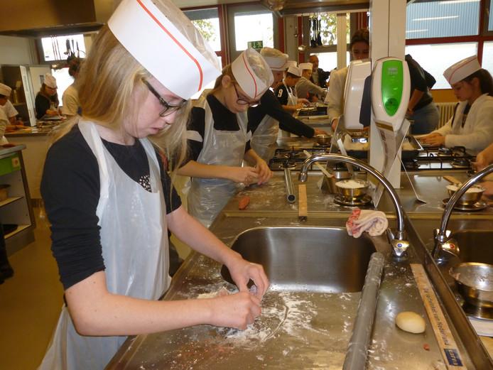 De 11-jarige Melissa is druk bezig met het rollen van haar worstenbroodjes.