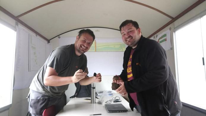 De archeologen Michael Bot (rechts) en Mart Louwerse tonen hun vondsten in de werkkeet bij de opgravingsplek.