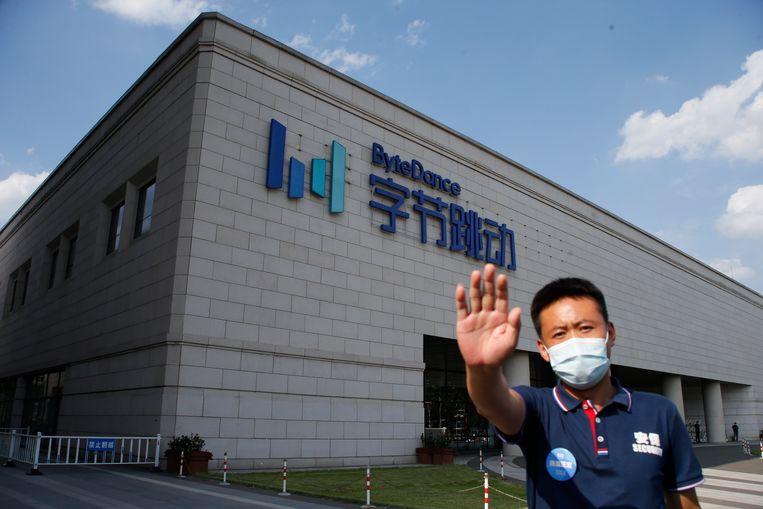 Een beveiliger probeert een fotograaf tegen te houden voor het hoofdkantoor van Bytedance, het bedrijf achter TikTok, in Beijing. Beeld EPA
