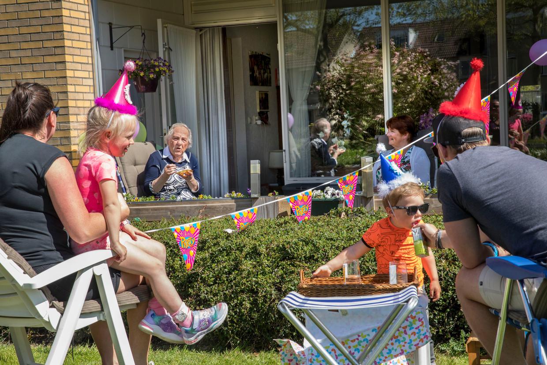 Mevrouw Blom is 89 jaar geworden. Haar kleinkinderen en achterkleinkinderen blijven vanwege corona aan de andere kant van de heg.  Beeld Arie Kievit